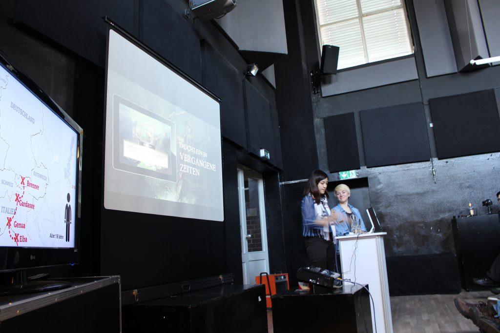 Zwei Studentinnen präsentieren ihr Projekt vor Publikum