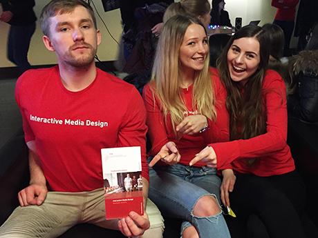 Drei Personen mit roten Shirt und weißer Aufschrift: Interactive Media Design auf dem hobit Stand. Zwei junge Frauen zeigen auf den Studiengangsflyer, den ein junger Mann in die Kamera hält.