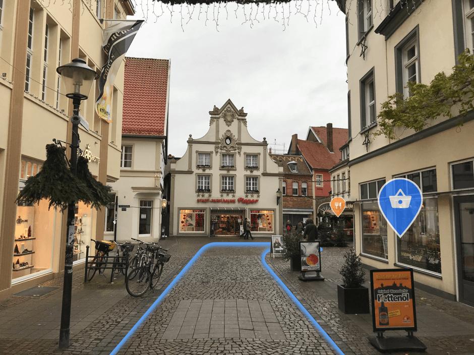 Straße innerorts mit blauen Leitlinien und Markern an Geschäften