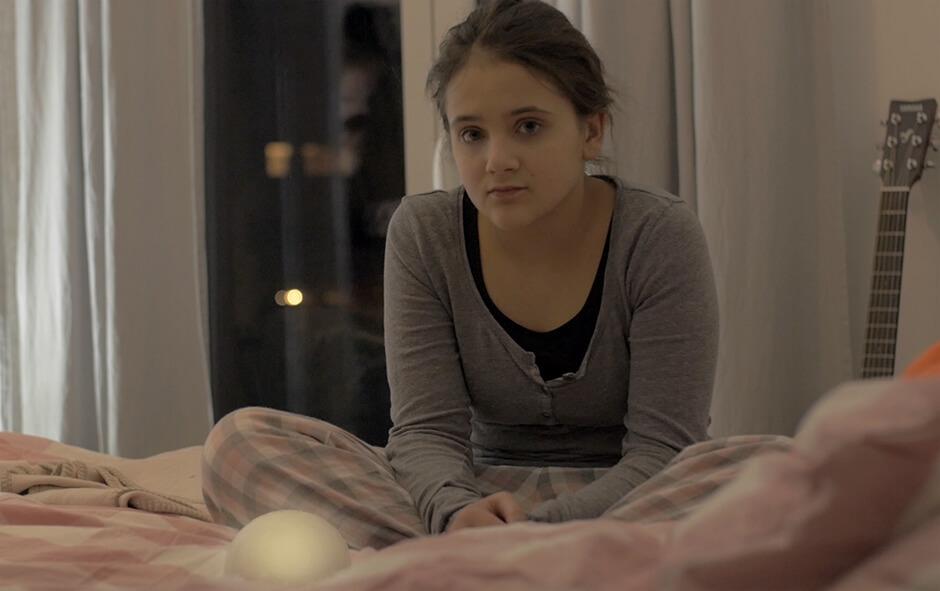 Ein Mädchen sitz im Schneidersitz auf einem Bett. Vor ihr steht WYN und leuchtet. Die Nutzungssituation am Abend soll dargestellt werden.