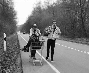 Das Projektteam (Hannah Ackermann, Davide Becker und Philipp Kaltofen) auf einer Landstraße. Hannah wird von Davide in einem Einkaufswagen geschoben.