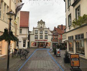 Blick auf eine Einkaufsstraße. Blaue Farbmarkierungen am Boden zeigen den Weg an.