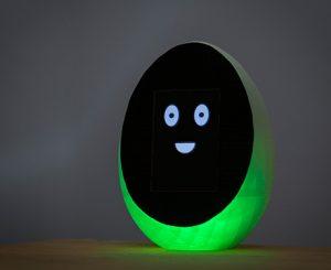 Das Balance-Ei Theo steht aufrecht. Es leuchtet grün und hat ein abstraktes, lachendes Gesicht auf schwarzem Hintergrund.