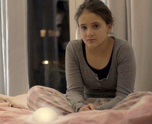 Junge Frau auf dem Bett sitzend mit dem Produkt WYN im Vordergrund