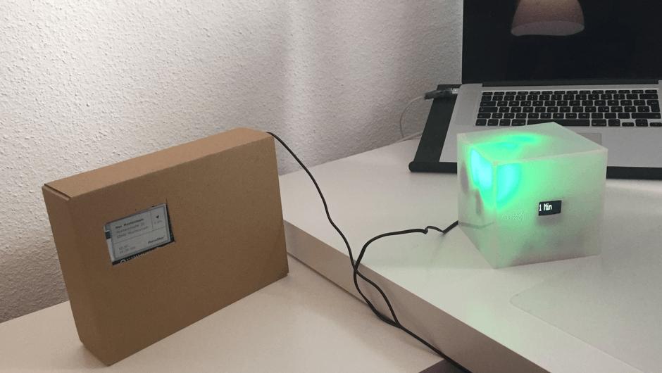 Man sieht ein Paket mit ParcelKey Tracker und den technischen Prototyp der grün leuchtet und eine Minute anzeigt.