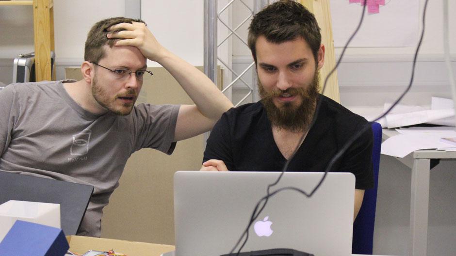 Man sieht Max, aus dem PArcelKey Team am Macbook. Neben ihm ist Herr Loenen, ein Professor zu sehen. Dieser schaut sehr überrascht und panisch zum Macbook.