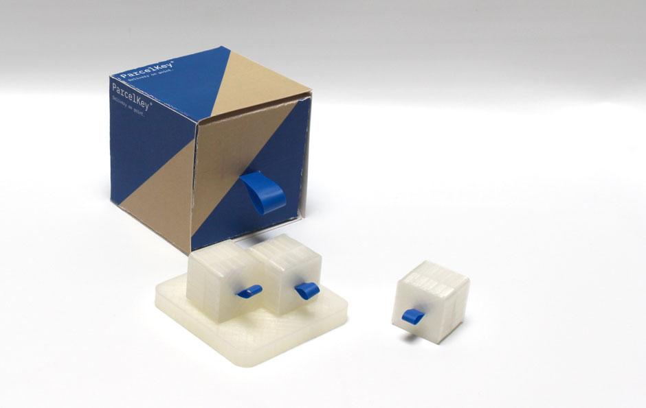 Man sieht die Verpackung in blau braun, sowie die ParcelKey Station und 3 ParcelKeys. Diese sind beide aus Plexiglas und bilden den Designprototyp.