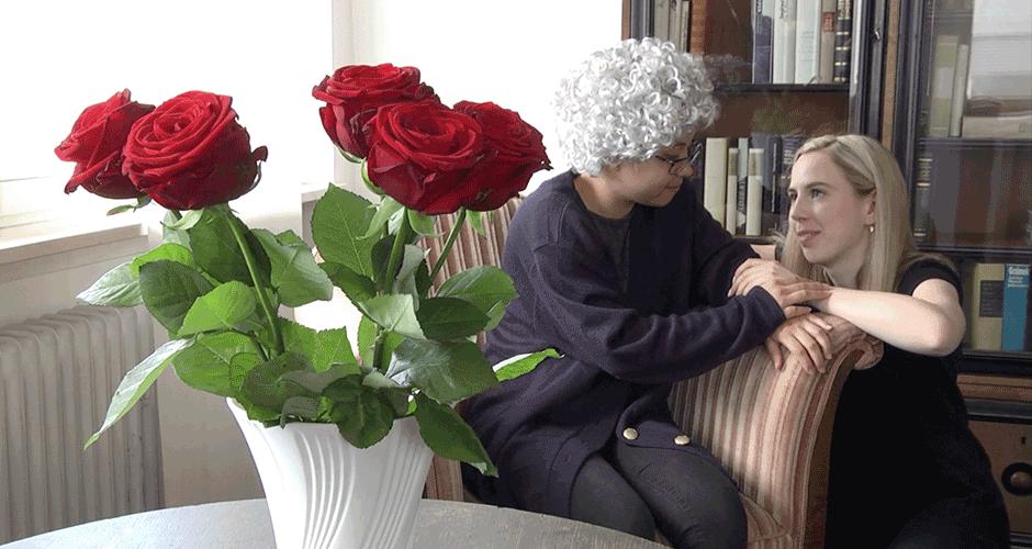 Im Vordergrund stehen Rosen in einer weißen Vase. Im Hintergrund sind eine alte Dame und eine blonde, junge Frau zu sehen. Die alte Dame sitzt auf einem Sessel, während die junge Frau daneben hockt und sich auf die Armlehne des Sessels stützt. Sie halten sich die Hände, schauen sich an und lächeln.