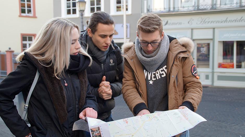 Spielergruppe hält eine Stadtkarte in der Hand