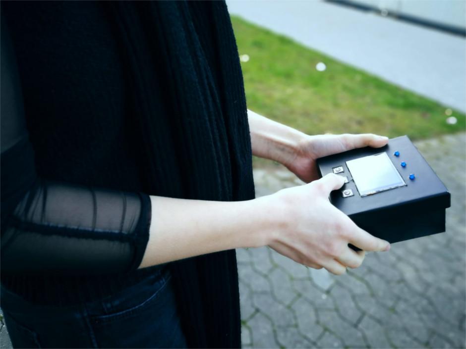 Frau hält kastenförmigen Funktionsprototypen mit Display in der Hand.