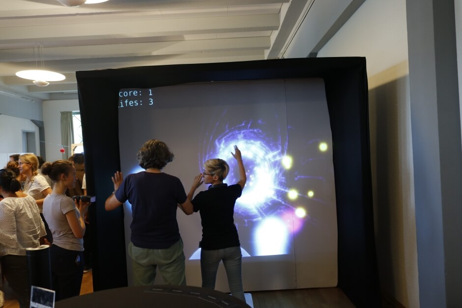 Besucher testen das Projekt Game Room, bei dem man auf die Wände projizierte Spielelemente durch Körperbewegungen manipulieren kann.