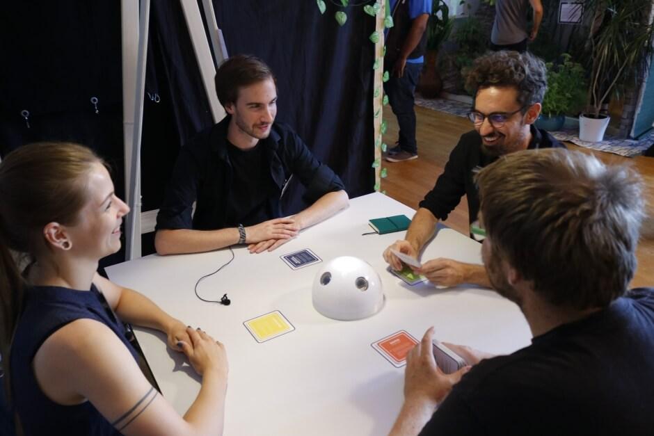 Vier Personen sitzen an einem runden Tisch. In der Mitte steht das kuppelförmige Interaktionselement des System Team-Flow