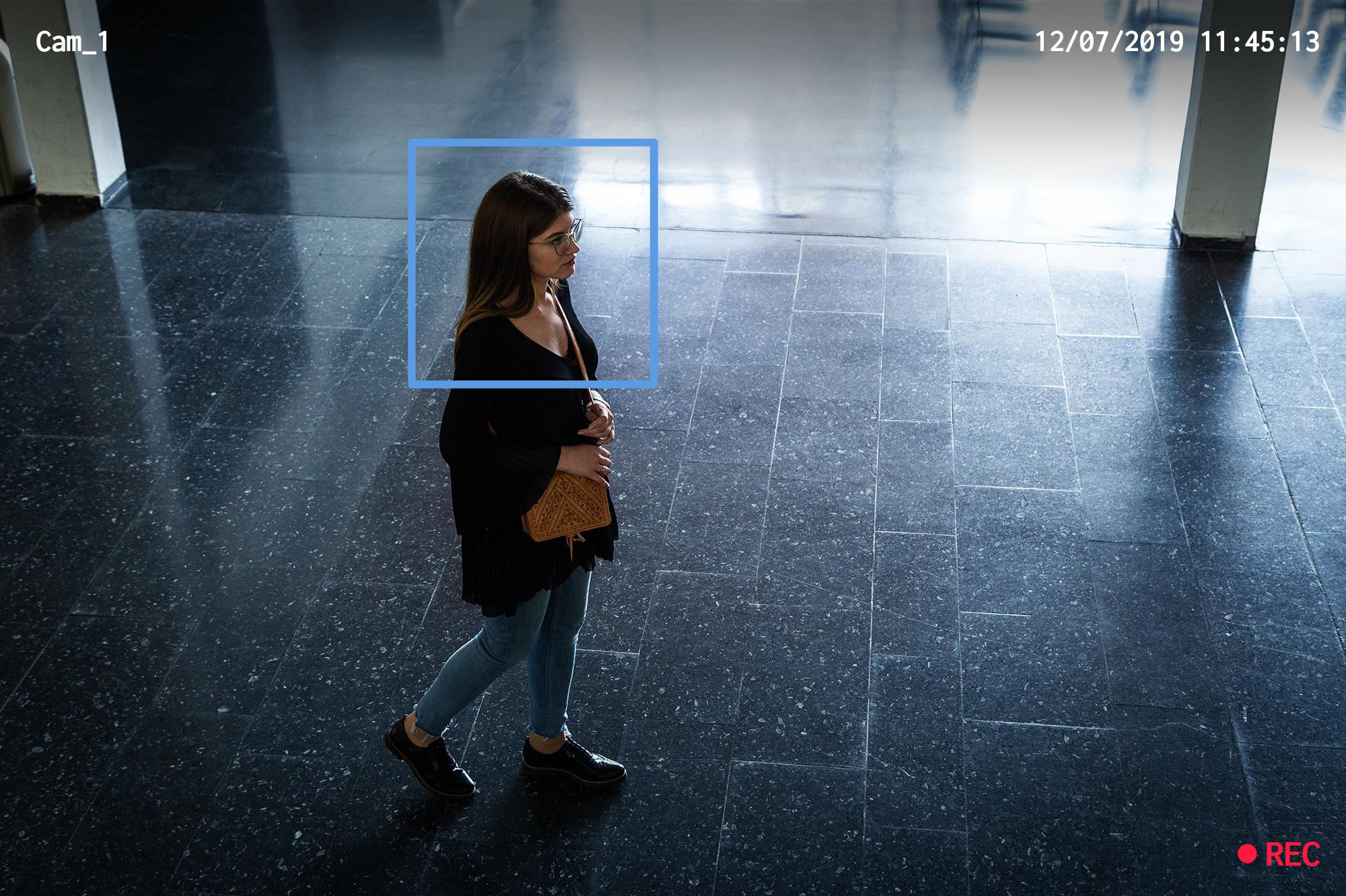 Eine Person die von links nach rechts durch ein Bild läuft und aus einer Überwachungskamera-Perspektive aufgenommen wird.
