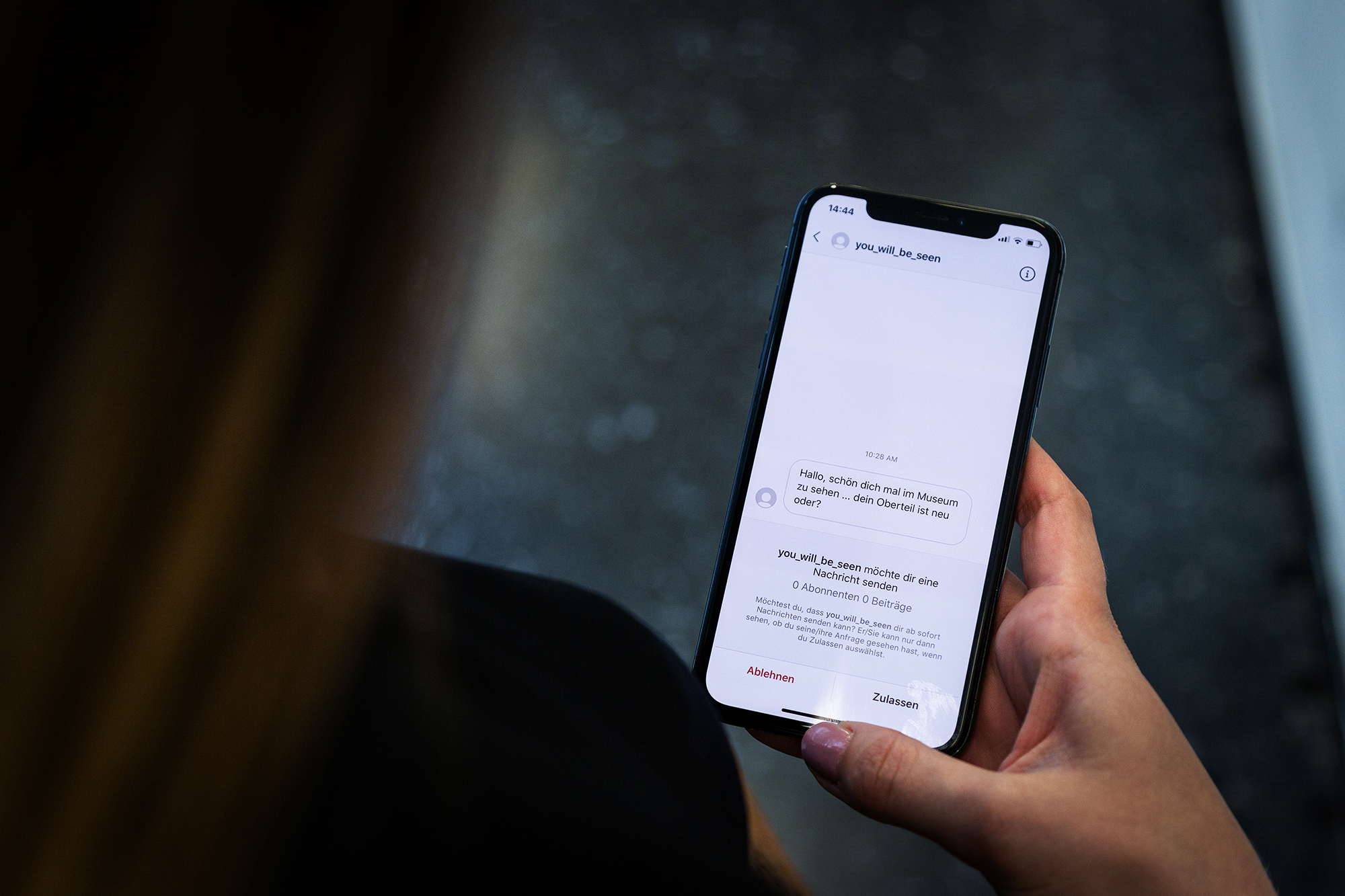 Eine Person hält ein Smartphone in der Hand auf dem man eine Nachricht von einem sozialen Netzwerk lesen kann.