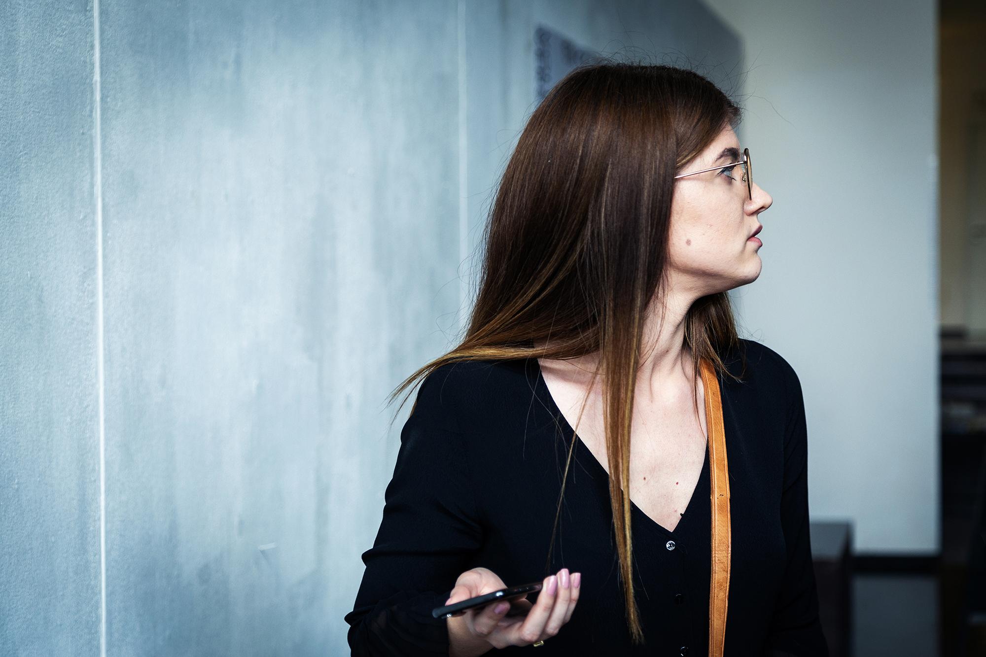 Eine Frau mit Smartphone in der Hand schaut sich verwirrt um.