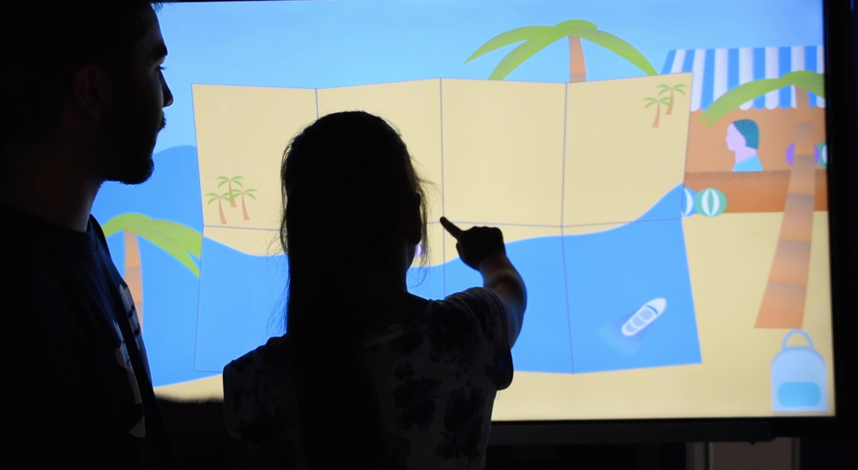 Auf dem Bild ist ein Kind seinem Vater, das auf einen großen Touchmonitor tippt. Auf dem Monitor läuft unser Spiel. Angezeigt wird eine Karte, auf der man sich das nächste Besuchsziel aussuchen kann.