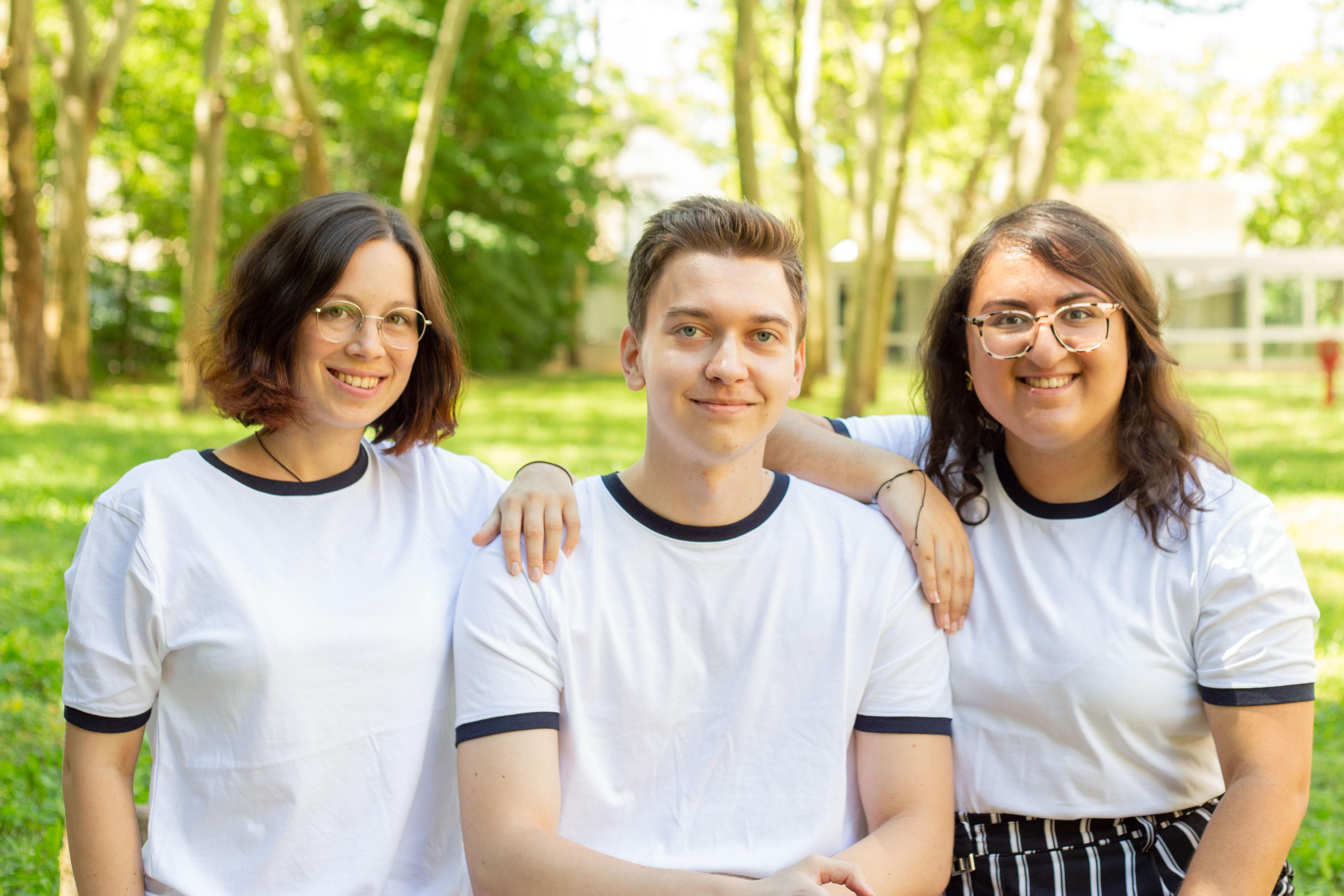 Gruppenfoto von Cowpanion vor einem grünen Hintergrund. Alle tragen das selbe weiß schwarze T-shirt