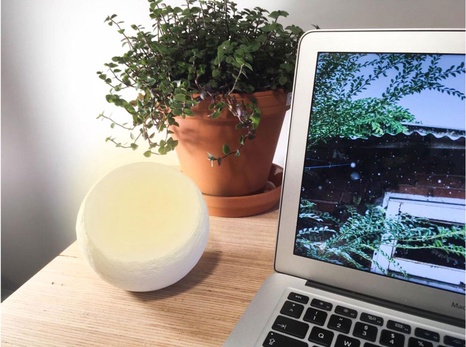 Die Nahaufnahme eines Schreibtischs. Ein Laptop steht im Vordergrund, dahinter eine Tischpflanze. Neben dem PC ist eine Kugel zu sehen. Sie hat eine schräge, abgeflachte Seite, die schwach leuchtet.