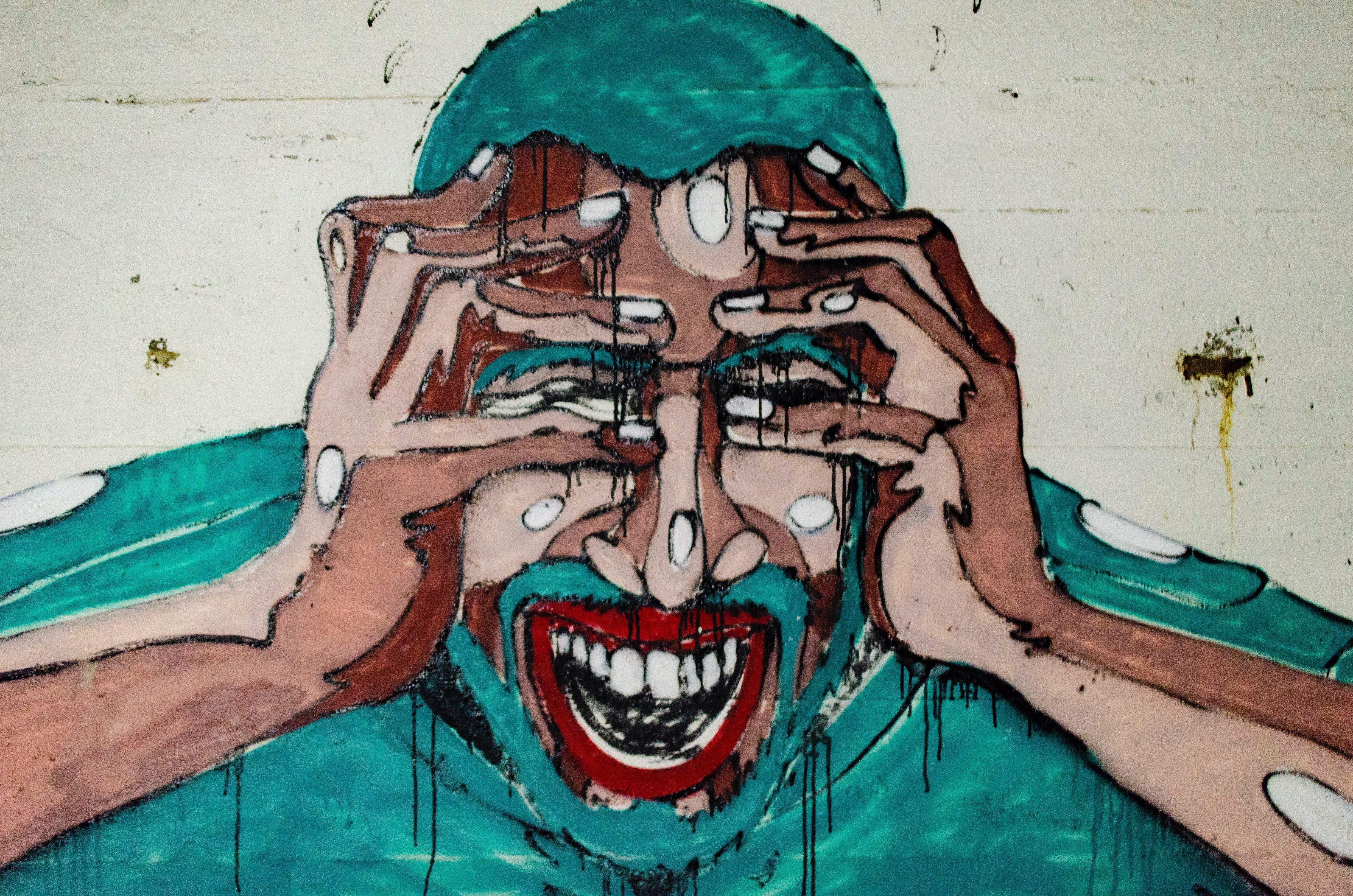 Graffiti auf dem ein Mann zu sehen ist, der den Mund aufreißt und sich die Hände an den Kopf hält.