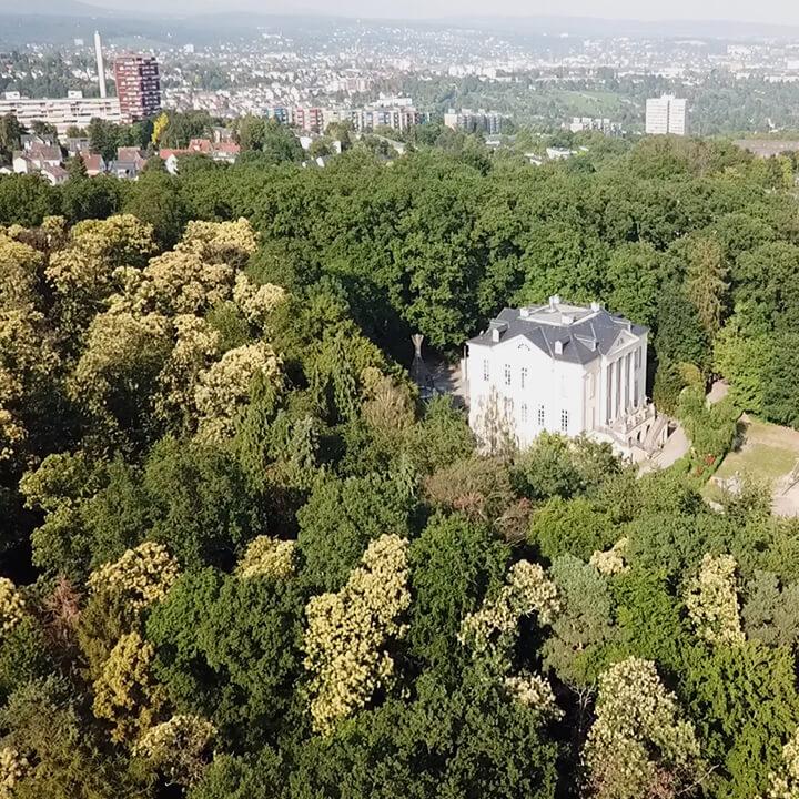 Drohnenaufnahme von Wald umgebenem Gebäude und Stadt im Hintergrund.
