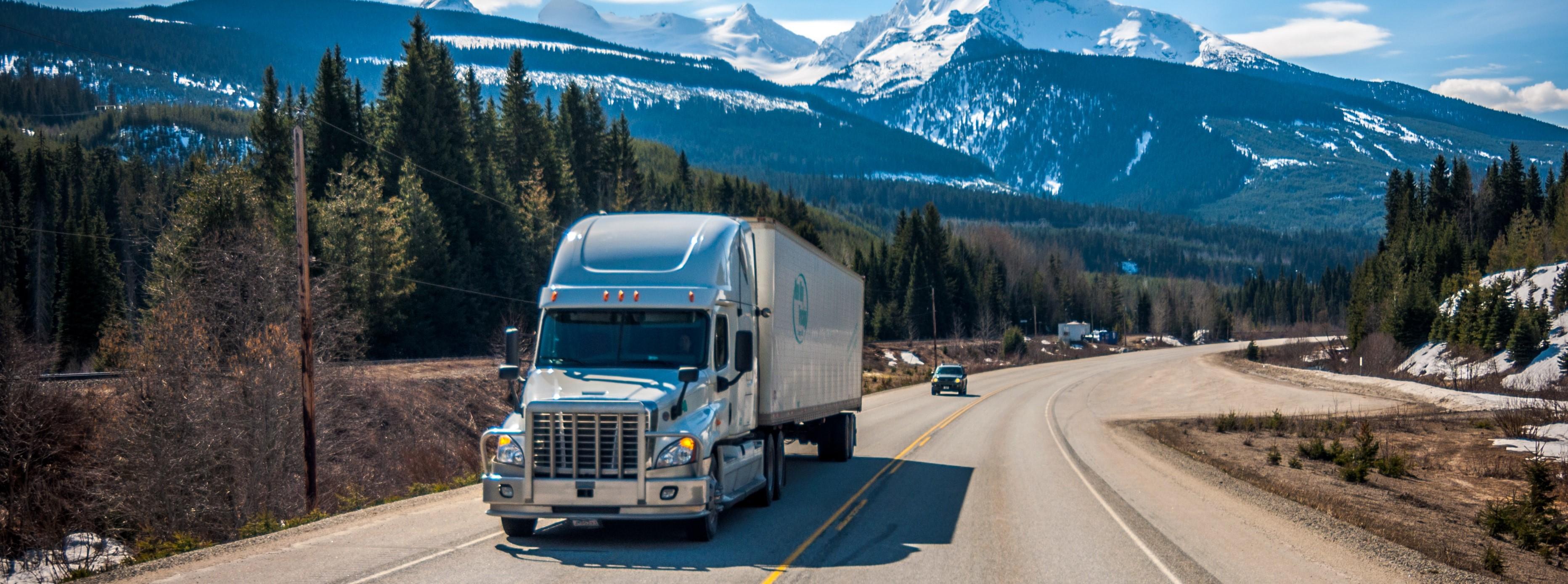 Ein Truck auf der Autobahn. Das Bild vermittelt die Freiheit des TRuckes auf der Landstraße. Im Hintergrund zu sehen ist eine gebirgskette mit Schnee auf den Gipfeln, darüner der blaue Himmel. Außer dem LKW im Vordergrund ist nur noch ein anderer PkW unterwegs.