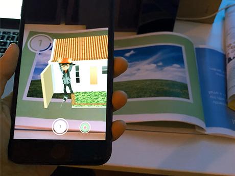 Ein Smartphone wird über ein Buch gehalten. Mit dessen Kamera wird nicht nur der Inhalt der auggeschlagenen Buchseite wiedergegeben, sondern auch ein kleiner Film, der Elias in der abgebildeten Umgebung zeigt. Hier tritt Elias gerade vor sein Haus in seinen Garten.