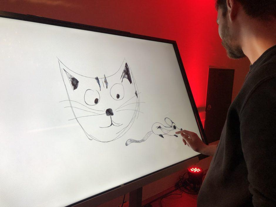 Junger Mann malt mit dem Finger eine Katze auf einen Bildschirm.