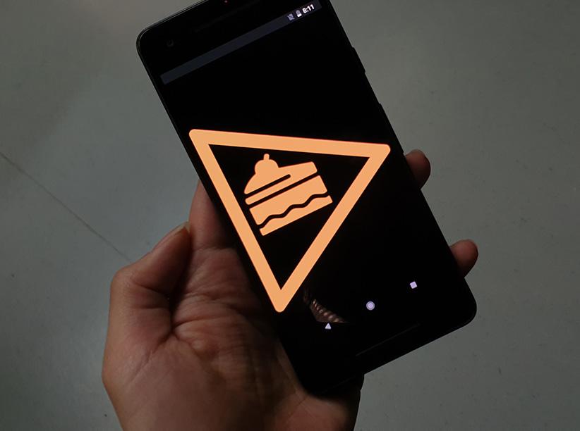 Eine Hand hält ein Handy auf dem ein Kuchen Symbol in der MItte eines Pfeils zu sehen ist