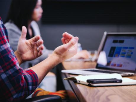 Close-Up von gestikulierenden Männerhänden. Im Hintergrund eine Frau an einem Schreibtisch arbeitend.