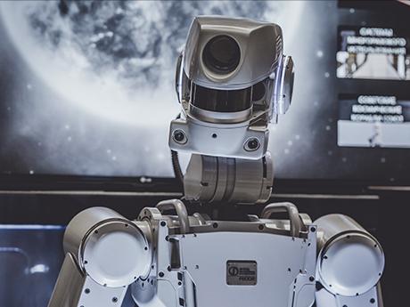 Weißer Roboter vor einem Großbildschirm mit einem Planeten.