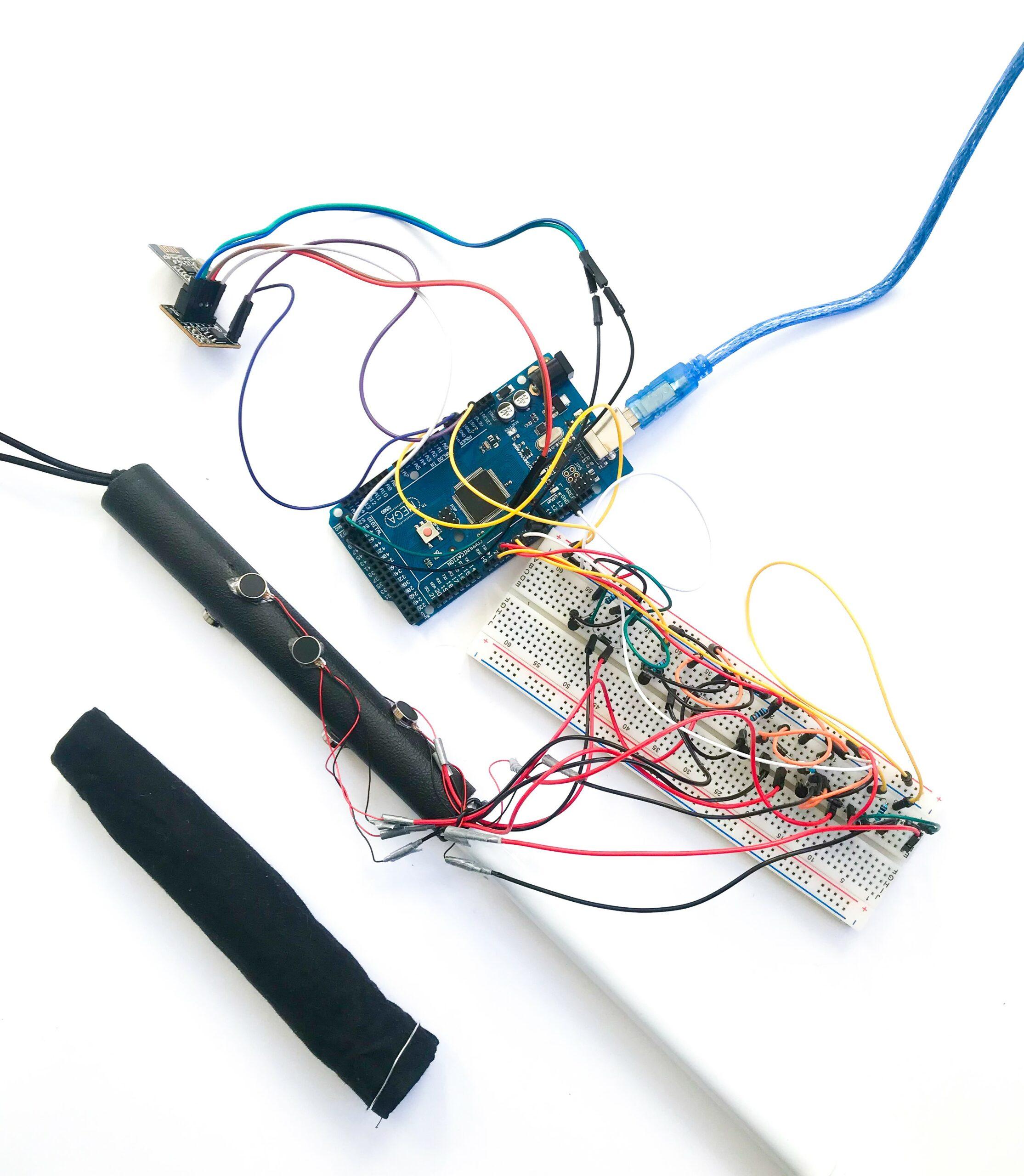 Der Prototyp von tactile. Es ist ein Blindenstock angebildet, welcher Vibrationsmotoren auf seinen Griff befestigt hat. Das Breadboard mit Arduino.